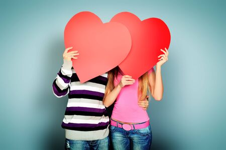 Happy young love couple posing together with red hearts.  photo