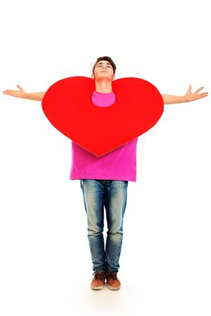 Happy young man posing with big red heart. Isolated over white background. photo