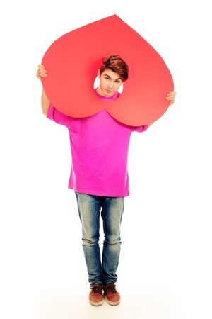 Emotional young man posing with big red heart. Isolated over white background. photo