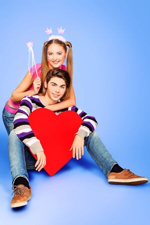 Happy young love couple posing together with red heart.