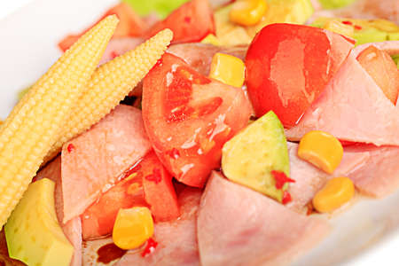 A plate of salad with vegetables and ham. Isolated on white. photo