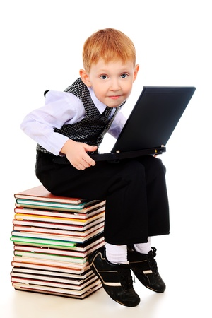 Shot of a boy learning with his books and laptop. Isolated over white background. photo