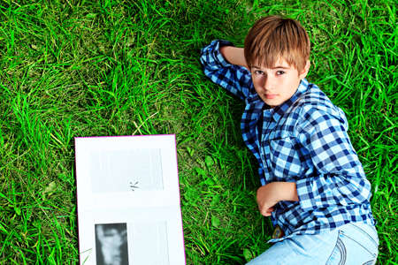 Shot of a  teenager boy with a book having a rest outdoor. photo