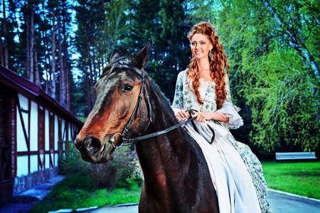 medieval dress: Joven y bella mujer en vestido medieval con un exterior de caballos.