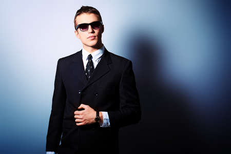 fashionable sunglasses: Portrait of a handsome young man in a suit. Shot in a studio.