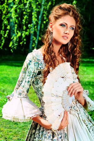 fantasy makeup: Hermosa mujer joven en traje de época medieval en un día soleado al aire libre.