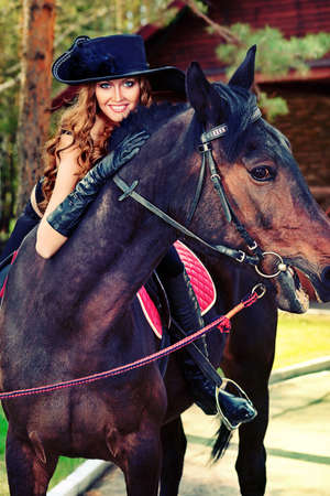 Beautiful young woman in medieval costume is riding on horseback. photo