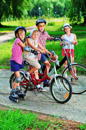bicycle helmet: Group of active children in a summer park. Stock Photo