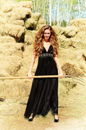 bewitch: Charming woman witch at a countryside.