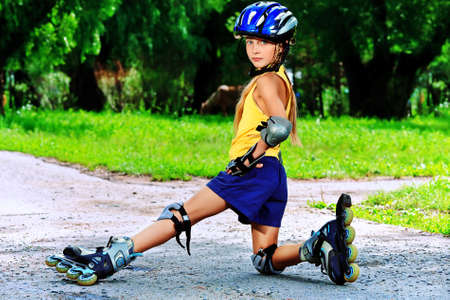 Little girl in roller skates at a park. photo