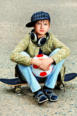 trendy: Portrait of a trendy boy teenager with skateboard and ball outdoors.