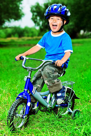 Happy boy on a bicycle in a summer park. photo