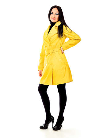 Fashion model in a coat posing at the studio. Isolated over white. photo