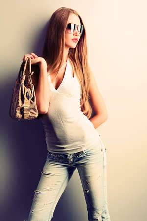 shades: Attractive young woman posing by the wall.