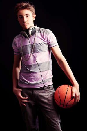 Young sportsman basketball player posing with ball. Over black background. photo