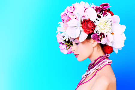 spring fashion: Portrait of a beautiful spring girl wearing flowers hat. Studio shot.