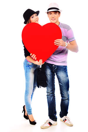 Portrait of a young loving couple holding big heart. Isolated over white. photo