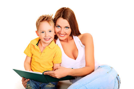Happy young mother and her son reading a book together. Isolated over white. photo