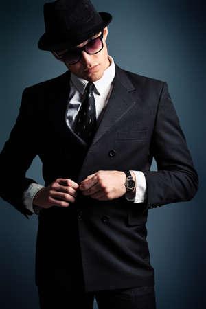 hombre con sombrero: Retrato de un hombre joven y guapo con un traje a tiros en un estudio