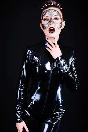 skinny woman: Conceptual shot of a woman in black glossy overall and metal buttons on her face