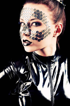 latex girl: Conceptual shot of a woman in black glossy overall and metal buttons on her face