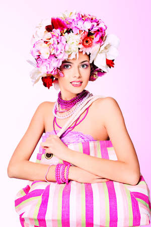 Portrait of a beautiful spring girl wearing flowers hat. Studio shot.