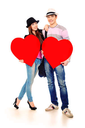two hearts: Portrait of a young loving couple holding big hearts. Isolated over white. Stock Photo