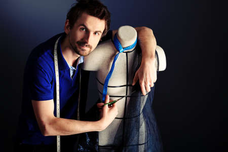 Portrait of a man fashion designer working with dummy at studio. Stock Photo - 13490424