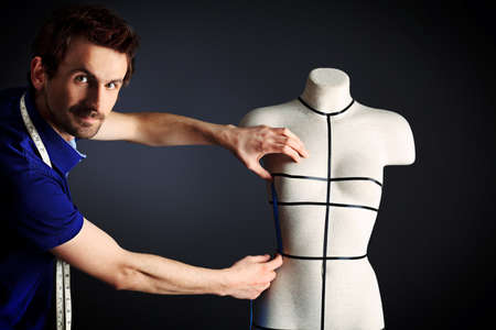 haute: Portrait of a man fashion designer working with dummy at studio. Stock Photo