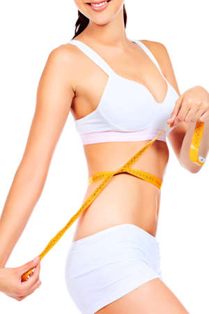 woman measuring: Slender woman measuring her waist. Diet, healthy lifestyle. Stock Photo