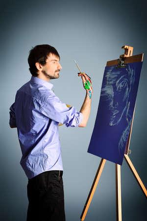 Retrato de un artista en la pintura de caballete. Filmada en un estudio.