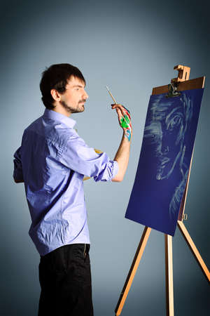 easel: Portrait of an artist painting on easel. Shot in a studio.