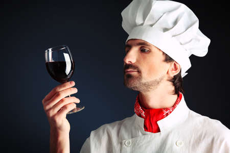 Portrait of a man cook holding a glass of red wine. Shot in a studio. photo