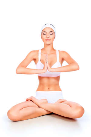 Portrait of a sporty young woman doing yoga exercise. Isolated over white background. photo