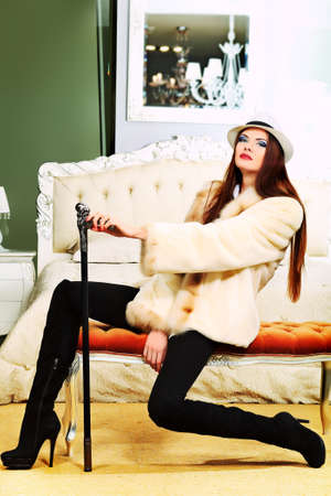 An attractive fashionable woman posing in the interior. photo