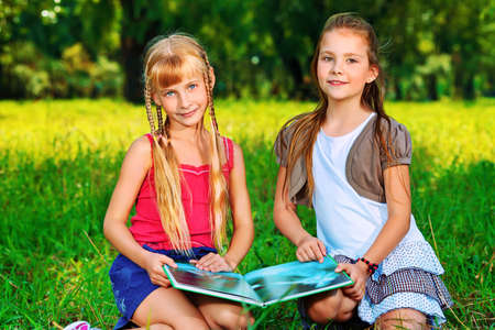 young schoolgirl: Two cheerful girls having fun outdoors. Stock Photo