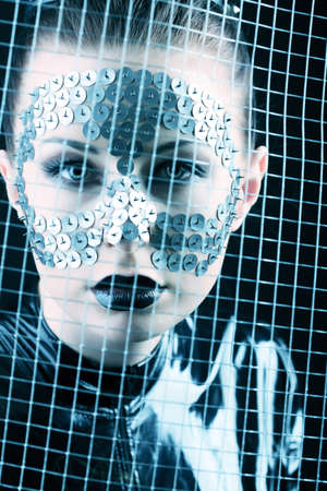 Conceptual shot of a woman in black glossy overall and metal buttons on her face. photo