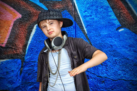 Portrait of a trendy boy teenager with headphones outdoors. photo