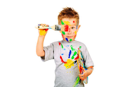 Portrait of a little boy enjoying his painting. Education. Isolated over white background.