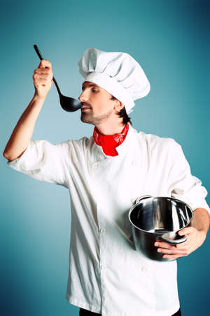 Portrait of a man cook holding a saucepan and ladle. Shot in a studio. photo