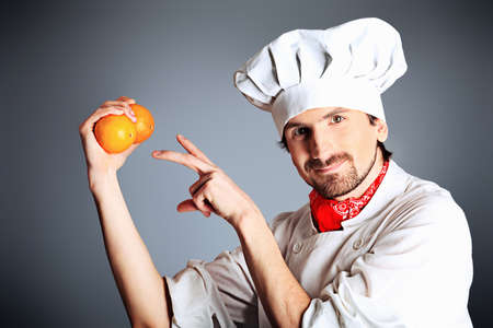 Portrait of a man cook holding oranges. Shot in a studio. photo