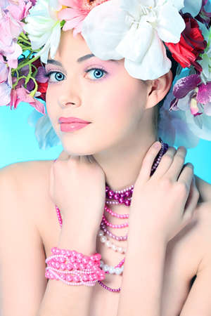 Portrait of a beautiful spring girl wearing flowers hat. Studio shot. photo