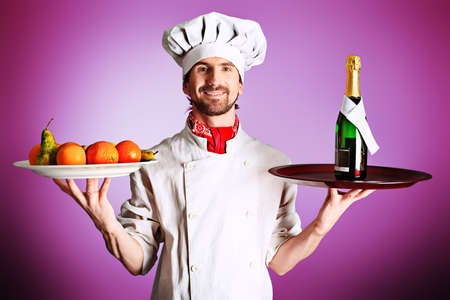 Portrait of a man cook holding a bottle of champagne and fruits. Shot in a studio. photo