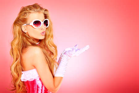 stay beautiful: Portrait of a charming blonde woman posing in studio over pink background.