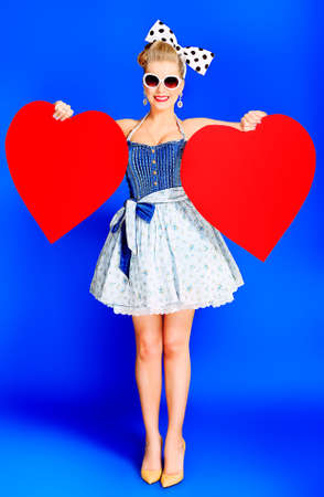 Beautiful young woman with pin-up make-up and hairstyle posing in studio with red hearts. Stock Photo - 13637410