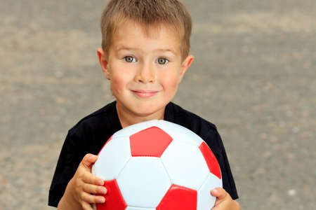 boy ball: Shot of a cute laughing boy with a ball outdoor.