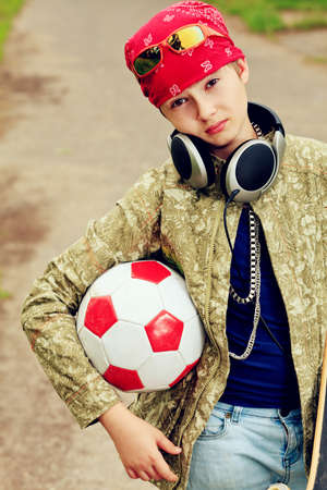 Portrait of a trendy boy teenager with skateboard and ball outdoors. photo