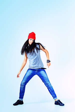 Modern teenage girl dancing hip-hop at studio. Isolated over white background. photo