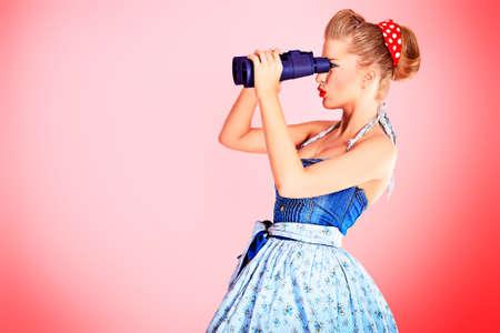Hermosa mujer joven con pin-up maquillaje y peinado mirando a través de binoculares.