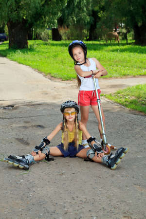 Happy girls with roller and scooter in a summer park. photo